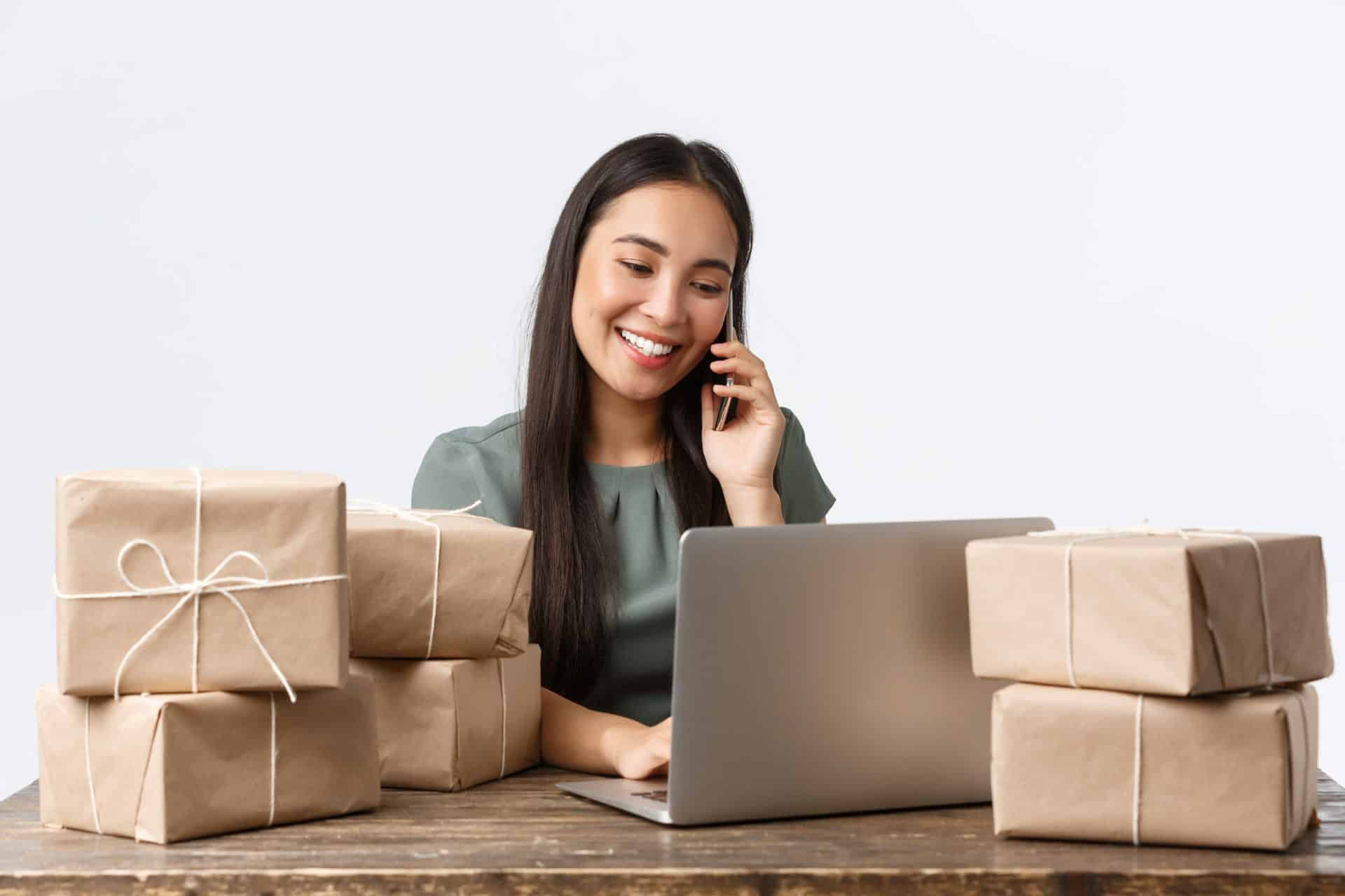 woman business owner with a laptop surrounded by packages