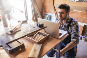 Small business owner in workshop sitting at workbench looking at laptop with questioning look