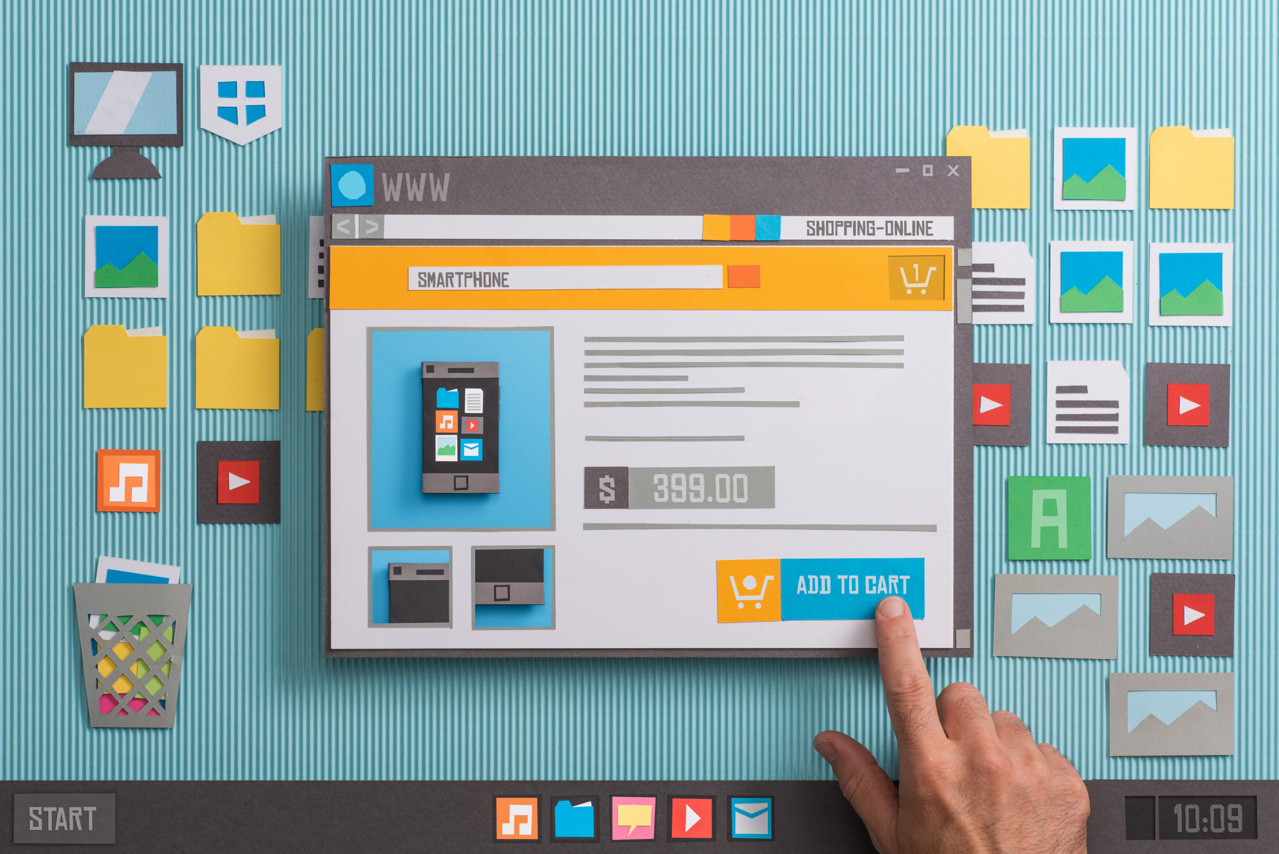 Persons hand pointing to Add to Cart button on large paper cutout of website design layout.