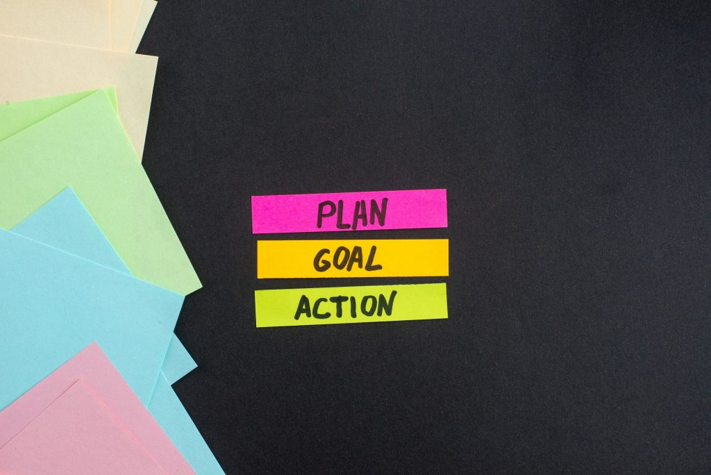 three sticky notes with plan, goal, action written